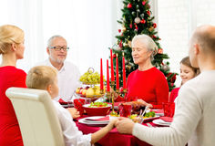 Smiling family having holiday dinner at home. Family, holidays, generation, christmas and people concept - smiling family having dinner and praying at home Stock Images