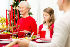 Smiling family having holiday dinner at home. Family, holidays, generation, christmas and people concept - smiling family having dinner and praying at home Royalty Free Stock Image