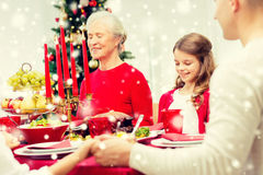 Smiling family having holiday dinner at home. Family, holidays, generation, christmas and people concept - smiling family having dinner and praying at home stock photography