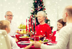Smiling family having holiday dinner at home. Family, holidays, generation, christmas and people concept - smiling family having dinner and praying at home royalty free stock photography