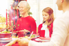 Smiling family having holiday dinner at home. Family, holidays, generation, christmas and people concept - smiling family having dinner and praying at home stock photos