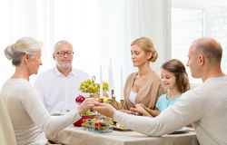 Smiling family having holiday dinner at home. Family, holidays, generation and people concept - smiling family having dinner and praying at home Royalty Free Stock Image