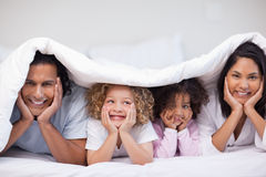 Smiling family hiding under the blanket Royalty Free Stock Image