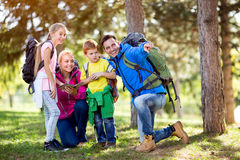 Smiling family on hiking shows with finger destination. In the forest Royalty Free Stock Photo