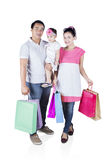 Smiling family hold shopping bag. Full length of smiling family holding shopping bag while smiling at the camera, isolated on white background Royalty Free Stock Photography