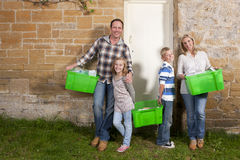 Smiling family holding bins full of recycling materials Royalty Free Stock Image