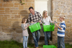 Smiling family holding bins full of recycling materials Royalty Free Stock Photography