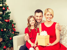 Smiling family holding gift box Stock Images