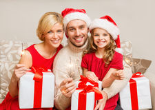 Smiling family holding gift boxes and sparkles Royalty Free Stock Images