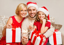 Smiling family holding gift boxes and sparkles Stock Photos