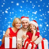Smiling family holding gift boxes and sparkles Stock Images