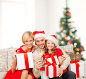 Smiling family holding gift boxes and sparkles Royalty Free Stock Image
