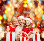 Smiling family holding gift boxes and sparkles Royalty Free Stock Photography