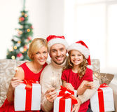 Smiling family holding gift boxes and sparkles Royalty Free Stock Photo