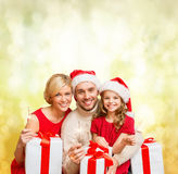 Smiling family holding gift boxes and sparkles Stock Image