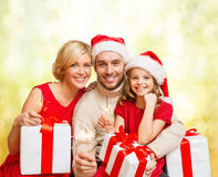 Smiling family holding gift boxes and sparkles Stock Photography