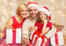 Smiling family holding gift boxes and sparkles Royalty Free Stock Photos