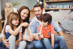 Smiling family holding house shape at home royalty free stock images
