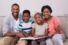 Smiling family holding magazine while sitting on sofa at home Royalty Free Stock Images
