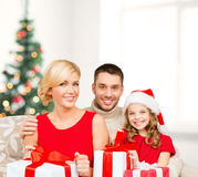 Smiling family holding many gift boxes Stock Images