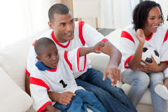 Smiling family holding a soccer ball. Smiling Afro-american family holding a soccer ball on the sofa Royalty Free Stock Image