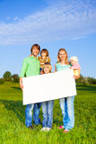 Smiling family holds white square paper format Royalty Free Stock Image