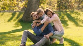 Smiling family hugging each other, while sitting on green field stock footage
