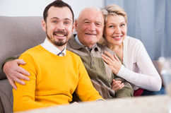 Smiling family hugging sitting on sofa. Smiling grandfather, grandson and his mother hugging sitting on sofa at home Stock Photos