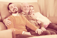 Smiling family hugging sitting on sofa. Smiling grandfather, grandson and his mother hugging sitting on sofa at home Royalty Free Stock Photography