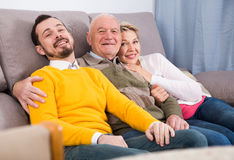 Smiling family hugging sitting on sofa. Smiling grandfather, grandson and his mother hugging sitting on sofa at home Royalty Free Stock Image