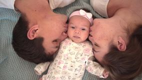 Free Smiling Family In Bed, Where The Cool Face Plan Is Dad, Mom And Little Daughter, Parents Gently Kiss Their Baby. Stock Photo - 144707200