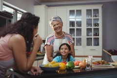 Smiling family interacting with each other in kitchen Royalty Free Stock Photos