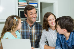 Smiling family interacting with each other while using laptop in living room. At home Royalty Free Stock Image