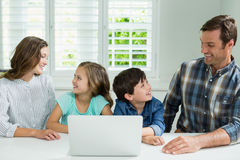 Smiling family interacting with each other while using laptop in living room. At home Stock Photos