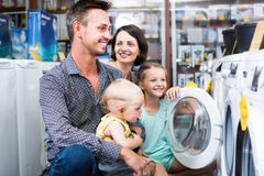 Smiling family with kids shopping washing machine Royalty Free Stock Photos