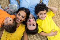 Smiling family laying on carpet Royalty Free Stock Images