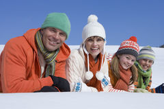 Smiling family laying in snow together Stock Photo