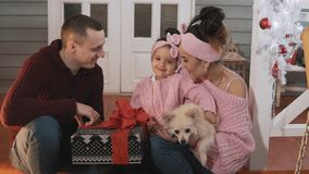 Smiling family with little daughter and dog sitting on porch with Christmas tree. Young family pack gifts for Christmas. Portrait of smiling family with little stock footage