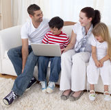 Smiling family in living-room using a laptop. Sitting on sofa Royalty Free Stock Photography