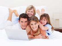 Smiling family looking at a laptop lying on bed Royalty Free Stock Photography