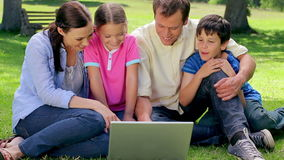 Smiling family looking at a laptop together Royalty Free Stock Photography