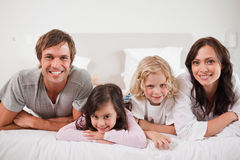 Smiling family lying in a bed Stock Photos