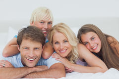 Smiling family lying on bed. Smiling family lying together on bed Royalty Free Stock Photo
