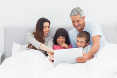 Smiling family lying in bed using their laptop Royalty Free Stock Photo