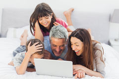 Smiling family lying on bed using their laptop. At home Stock Photos