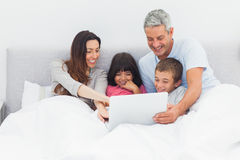 Smiling family lying in bed using their laptop Stock Photography