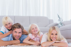 Smiling family lying on the carpet Stock Photos