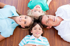 Smiling family lying in circle on the floor Royalty Free Stock Images