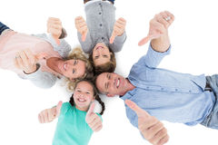 Smiling family lying on the floor in a circle showing thumbs up Royalty Free Stock Photo
