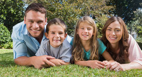 Smiling family lying on the grass. Looking at camera in the park Royalty Free Stock Photography